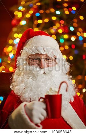 Santa Claus holding red cup with latte on background of sparkling xmas tree
