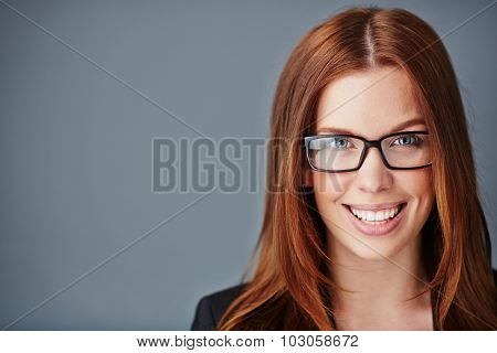 Young businesswoman in eyeglasses looking at camera with toothy smile