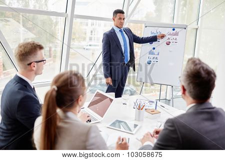 Confident businessman explaining data on board to colleagues in office