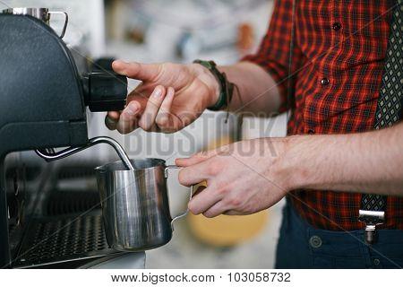 Barista holding metallic mug while using coffee machine