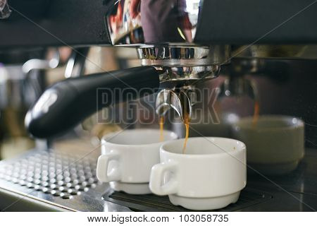 Espresso pouring in two porcelain cups from coffee machine