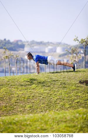 Man exercising with push ups in a Lisbon public park