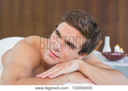 Handsome young man lying on massage table at spa center