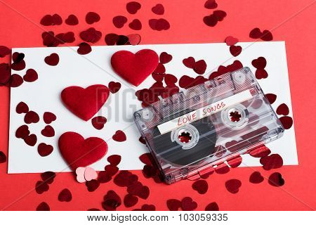 Audio Cassette Tape On Red Background With Fabric Heart