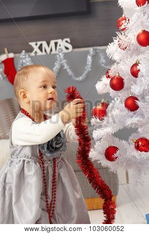 Pretty little girl decorating christmas tree at home.