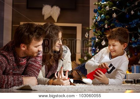 Happy family playing together with little dachshund puppy at christmas time.