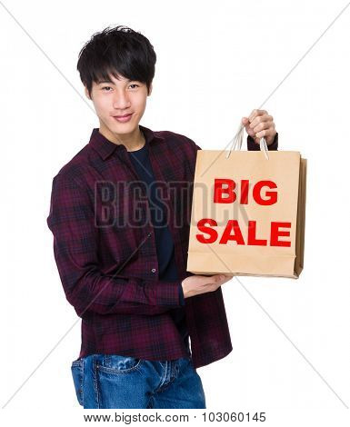 Young Man hold with shopping bag for showing phrase of big sale