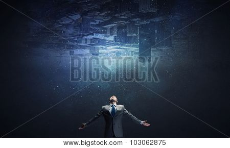 Businessman with hands spread apart and city reflection in sky