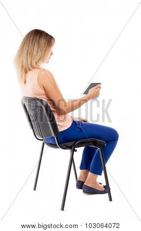 back view of woman sitting on chair and looks at the screen of the tablet.  Rear view people collection.  backside view person. Blonde in blue pants and pink sitting on a chair and looks into tablet