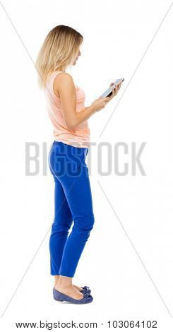 back view of standing young beautiful. girl with tablet computer in hands of. girl  watching. Rear view people collection. Blonde in blue pants and pink blouse stands sideways and looking at tablet.