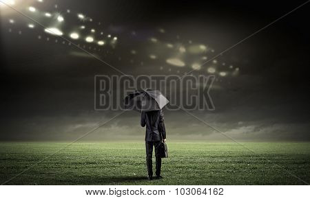 Back view of businessman with suitcase under umbrella