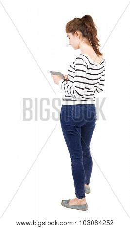 back view of standing young beautiful  girl with tablet computer in hands of. girl  watching. Rear view people collection. Isolated over white background. Girl in white striped jacket bent over plate