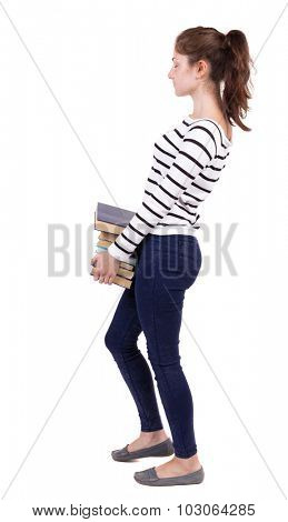 Girl comes with  stack of books.back view. Rear view people collection.  backside view of person.  Isolated over white background. Girl in white striped jacket carries heavy books