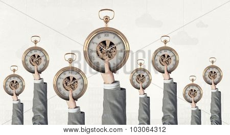 Many hands of business people holding pocket watch