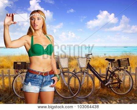 Blond tourist selfie photo smartphone in a beach with bicycles at Formentera photomount