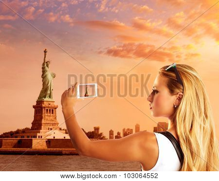 Blond tourist taking photo to Statue of Liberty in New York photomount