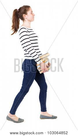 Girl comes with  stack of books.back view. Rear view people collection.  backside view of person.  Isolated over white background. Girl in white striped sweater unhappy carries the book to the right.