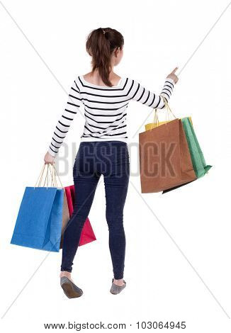 back view of woman  with shopping bags pointing . beautiful brunette girl in motion.  backside view of person.  Rear view people collection. Isolated over white background.