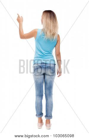 Back view of  pointing woman. beautiful girl. Rear view people collection.  backside view of person.  Isolated over white background. The girl in jeans and a blue shirt shows a finger of his left hand