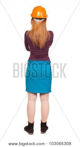 Backview of an woman engineer in construction helmet stands. Standing young woman. Rear view people collection.  backside view of person.  Isolated over white background.