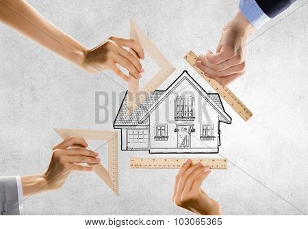 Close up of people hands measuring house model with ruler