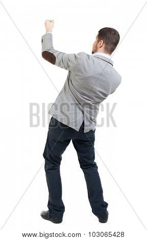 back view of standing man pulling a rope from the top or cling to something.  Rear view people collection.  backside view of person.  I