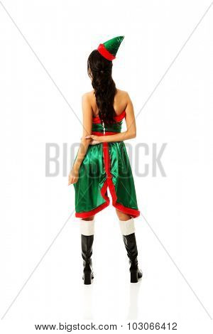 Woman wearing elf clothes standing back to camera.