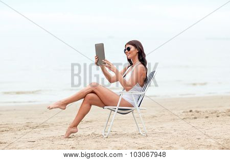 summer vacation, tourism, travel, holidays and people concept - smiling young woman with tablet pc computer sunbathing in lounge or folding chair on beach