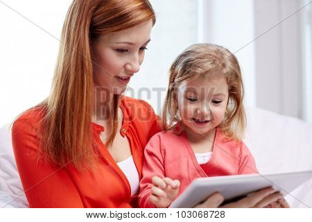 family, children, parenthood, technology and internet concept - happy mother and daughter with tablet pc computer at home