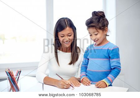 family, children, creativity and happy people concept - happy mother and daughter drawing with pencils at home or kindergarten