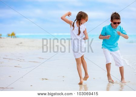Little kids having fun at tropical beach during summer vacation
