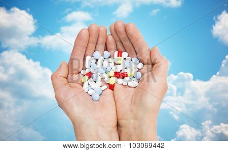 age, medicine, health care and people concept - close up of senior woman cupped hands with pills over blue sky and clouds background