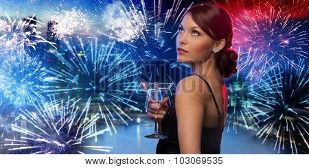 party, drinks, holidays, luxury and celebration concept - smiling woman in evening dress holding cocktail over nigh city and firework background