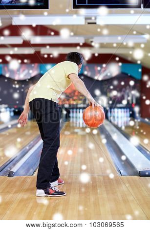 people, leisure, sport and entertainment concept - young man throwing ball in bowling club at winter season from back