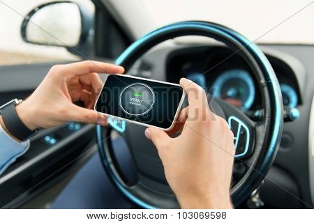 transport, business trip, technology and people concept - close up of male hands with start engine button on smartphone screen in car