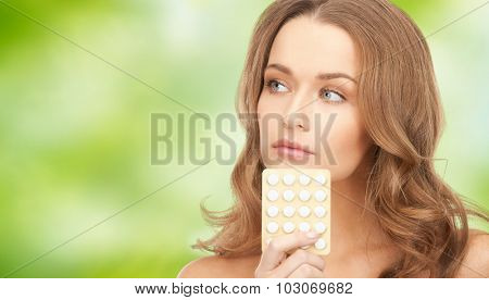 beauty, people, medicine and health care concept - beautiful young woman with medication over green natural background