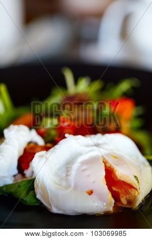 Poached eggs served for breakfast with vegetables, coffee and juice