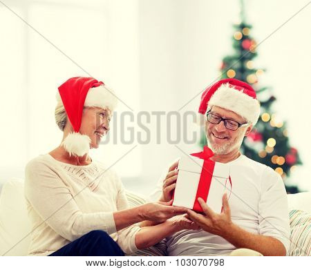 family, holidays, age and people concept - happy senior couple in santa helper hats with gift box over living room and christmas tree background