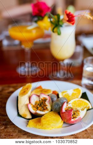 Exotic fruits platter amd tropical cocktailsserved at bar or restaurant