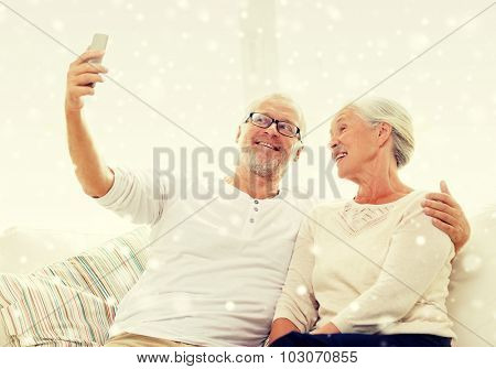 family, technology, age and people concept - happy senior couple with smartphone taking selfie at home