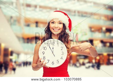 christmas, winter, holidays, time and people concept - smiling woman in santa helper hat and red dress with clock over shopping center background