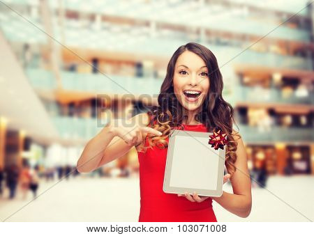 christmas, technology, present and people concept - smiling woman in red dress with blank tablet pc computer screen over shopping centre background