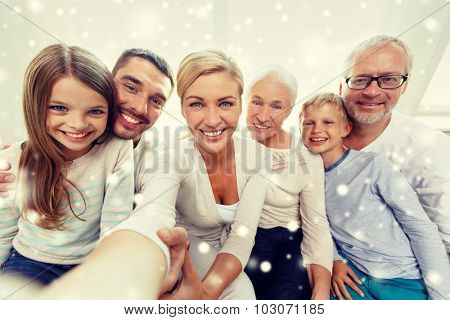 family, happiness, generation and people concept - happy family sitting on couch and taking selfie with camera or smartphone at home