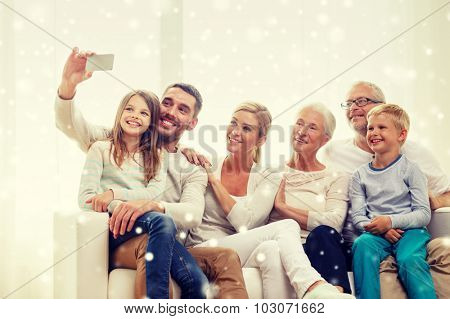 family, technology, generation and people concept - happy family sitting on couch and making selfie with smartphone at home