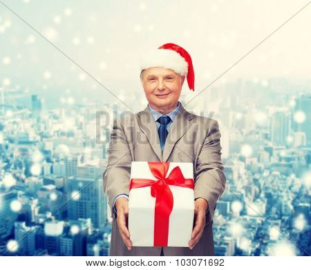 business, christmas, presents and people concept - smiling senior man in suit and santa helper hat with gift over snowy city background