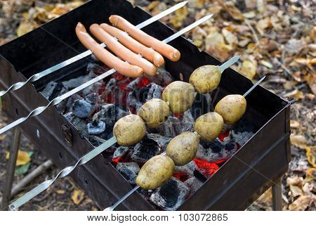 Potatoes And Sausages Fried On Coals In Grill