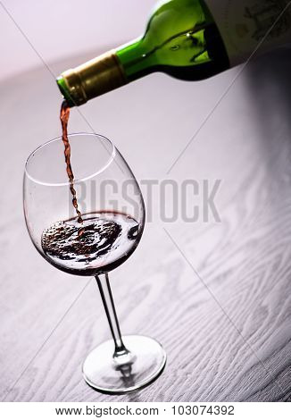 Red wine pouring into glass, close-up shot