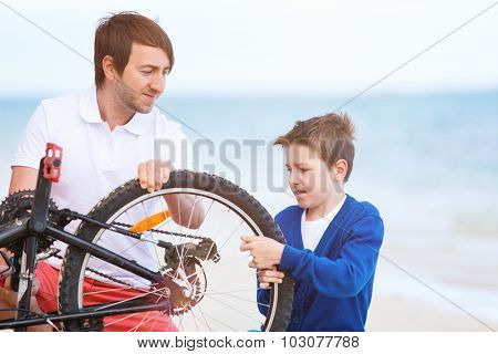 Teenage boy and his father repairing bicycle outdoors at summer