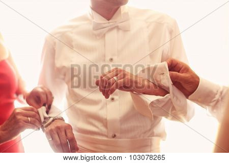 Groomsmen Helping The Groom Getting Ready For Wedding