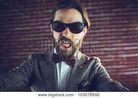 Portrait of angry fashionable man against brick wall